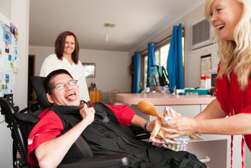 Young man with developmental disability in wheelchair being assisted to wipe dry a wooden spoon.