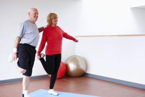 Senior Couple Balancing on One Leg and smiling