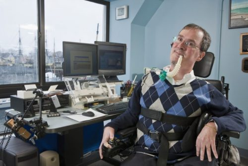 Businessman with Duchenne muscular dystrophy using a breathing ventilator in an office
