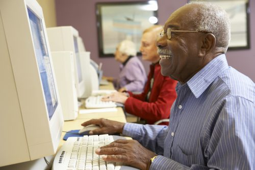 Senior man using computer in computer room smiling