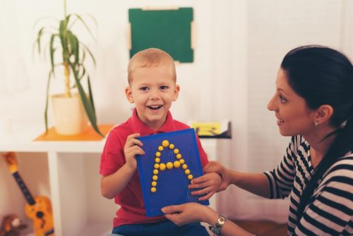 Little boy smiling during alphabet lesson with his speech therapist.