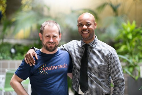 White man with blue Easterseals t-shirt has arm around African American man in patterned shirt and black tie