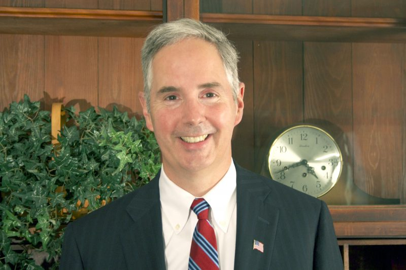 White man with gray hair in a business suit and patterned tie is smiling