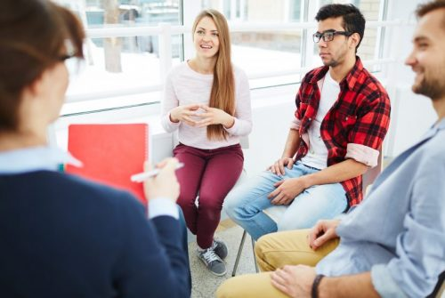 Group of young white people sitting in a therapy circle and sharing.