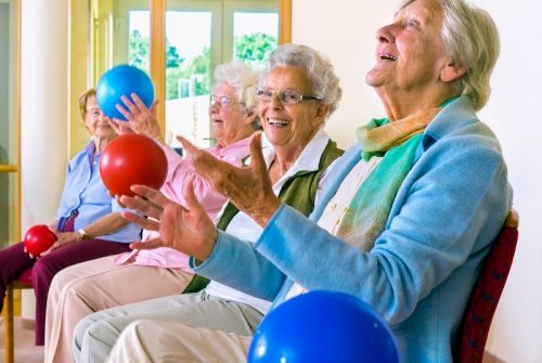 Group of happy elderly ladies in a seniors gym doing hand coordination exercises throwing and catching brightly colored plastic balls as they sit in their chairs.