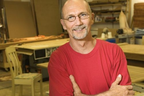 White man with glasses and goatee smiling, arms crossed, in workshop