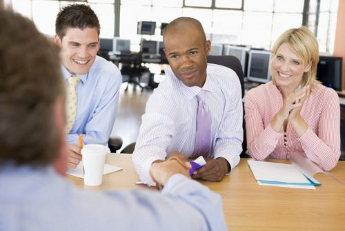 Three people in business attire, middle man is shaking applicant's hand across table