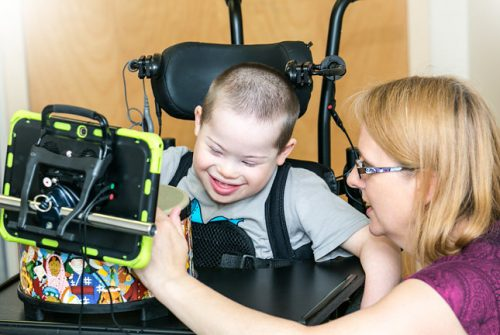 Young boy in wheelchair laughing, using drum technology with therapist helping