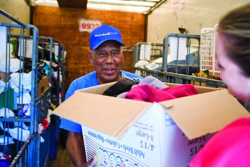 Goodwil trailer attendant is smiling and accepting a box of donations from someone.