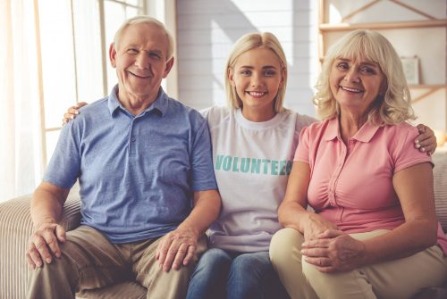 Beautiful young female volunteer and old couple are looking at camera and smiling while sitting on couch