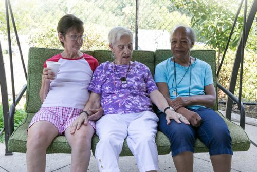 Three older ladies on a porch swing. Lady in middle has hands on the others' legs.