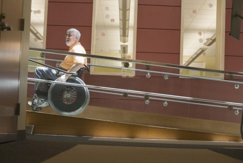 Older man using a wheelchair to go up a ramp