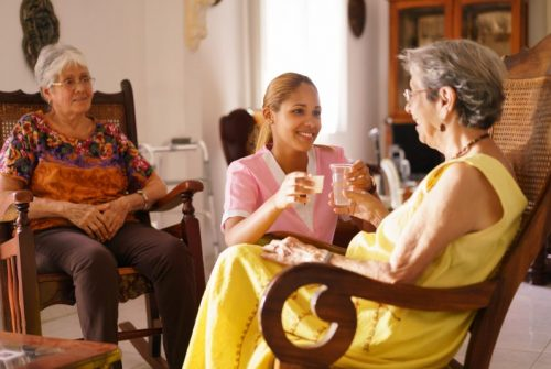 Young Hispanic woman working as nurse gives a water glass and prescription medicine to an older patient.