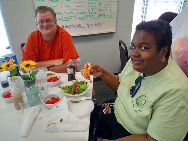 A white male and African American female smiling at the camera and enjoying pizza lunch