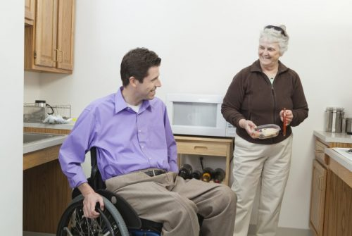 Man in wheelchair with spinal cord injury getting food from his home health aid