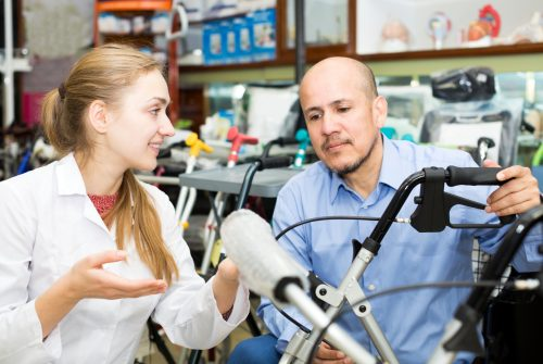 Cheerful female consultant offering wheelchair to customer in orthopaedic store