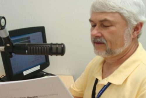 Older white man with beard looking at paper and reading into a microphone