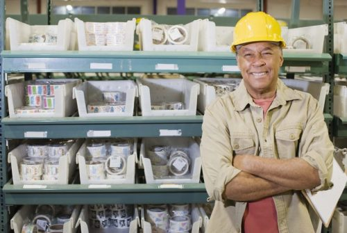 Older male factory worker stands next to parts, is smiling.