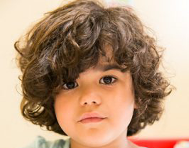 Young child with dark brown hair looking at you