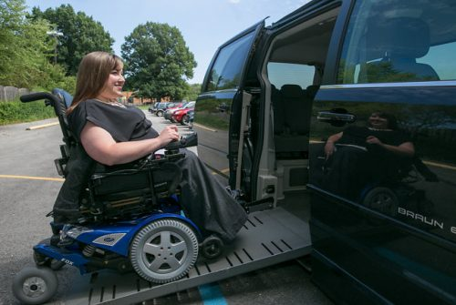 Woman in a motorized wheelchair is smiling and moving up a ramp into a van.