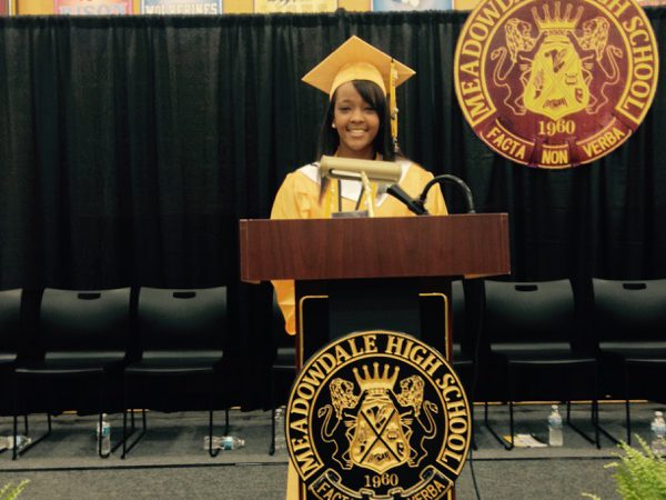 Young Black woman is GoodGuides mentor, standing at podium, wearing yellow high school graduation gown and cap.