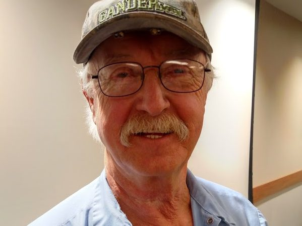 Older white man with glasses, moustache and ball cap. Is smiling.